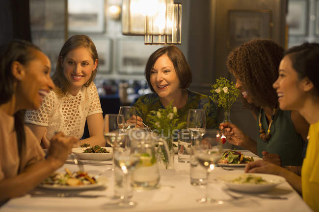 Smiling women friends dining at restaurant table — Stock Photo