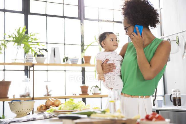 Матері, тримаючи її дочки дитини під час використання мобільного телефону у кухні — стокове фото