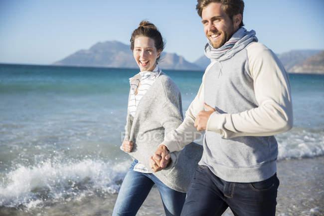 Молода пара, тримаючись за руки і прогулянки на пляж — стокове фото