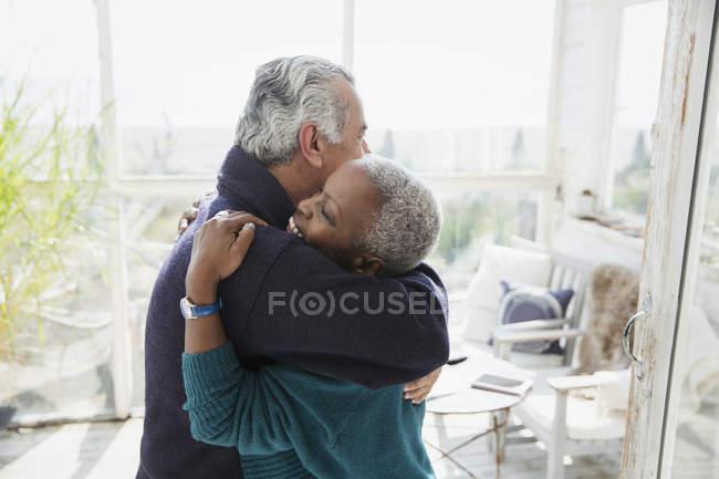 Affectionate senior couple hugging on sun porch — Stock Photo