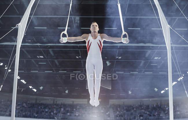 Мужской гимнаст балансирует с руками, вытянутыми на кольцах гимнастики на арене — стоковое фото