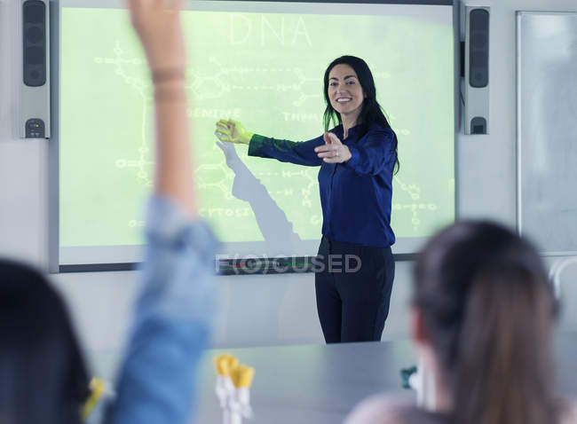 Smiling female science teacher leading lesson at projection screen in classroom — Stock Photo