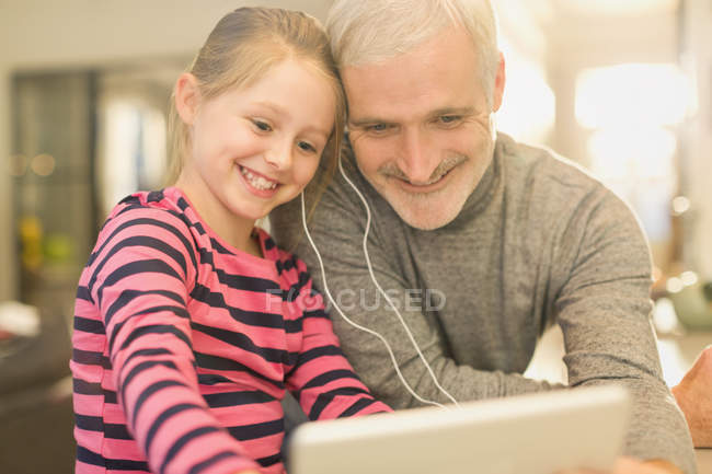 Smiling father and daughter sharing headphones, watching video on digital tablet — Stock Photo