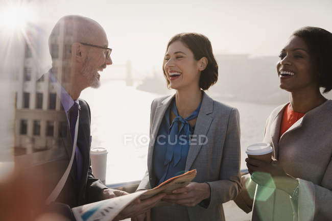 Silhouetted business people laughing, drinking coffee and reading newspaper on sunny urban bridge — Stock Photo