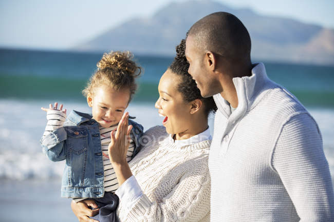 Happy family giving high five on beach — Stock Photo
