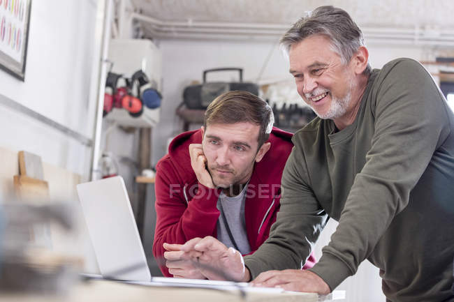 Male carpenters working at laptop in workshop — Stock Photo