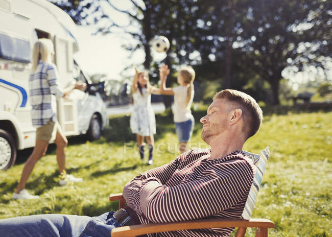 Serene father resting in lounge chair with family playing in background outside sunny motor home — Stock Photo