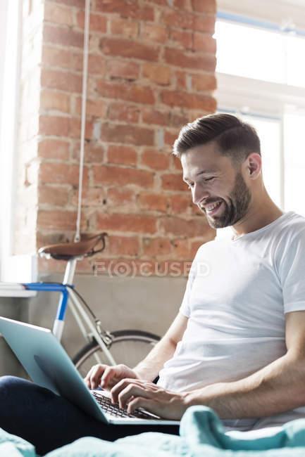 Uomo che utilizza il computer portatile sul letto — Foto stock