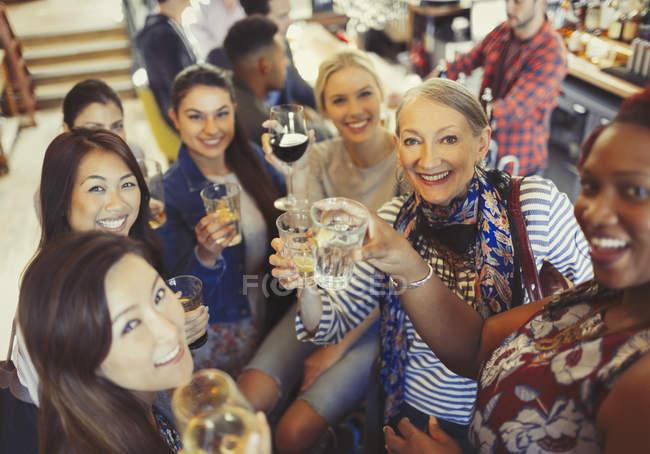 Porträt lächelnd, selbstbewusste Freundinnen, die an der Bar auf Bier und Weingläser anstoßen — Stockfoto