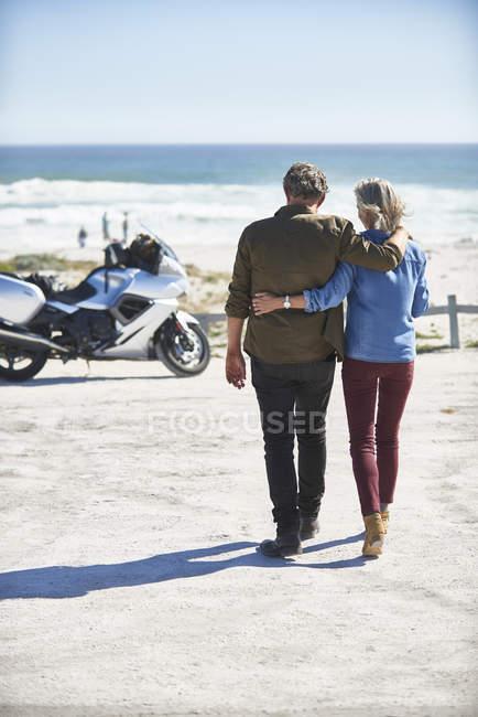 Ласкава старший пара ходьба на сонячному пляжі бік мотоцикл — стокове фото