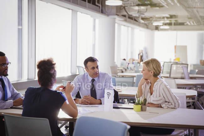 Empresários conversando à mesa no espaço de trabalho compartilhado — Fotografia de Stock