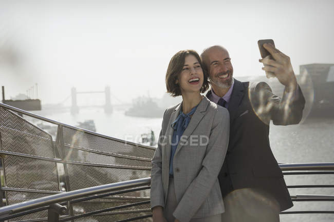 Enthusiastic, smiling business couple taking selfie with camera phone on sunny urban bridge, London, UK — стоковое фото