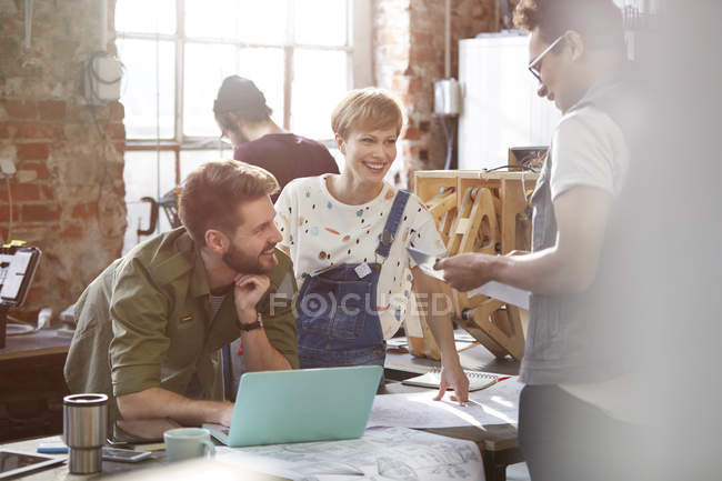 Designers meeting, discussing plans at laptop in workshop — Stock Photo