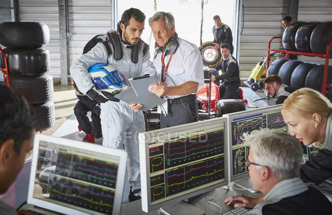 Manager und Formel-1-Fahrer diskutieren in Reparaturwerkstatt über Telemetrie-Diagnose — Stockfoto