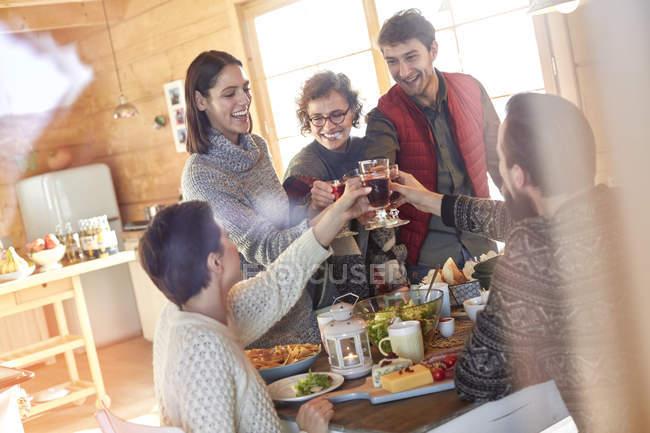 Freunde stoßen am Kabinentisch auf Weingläser an — Stockfoto