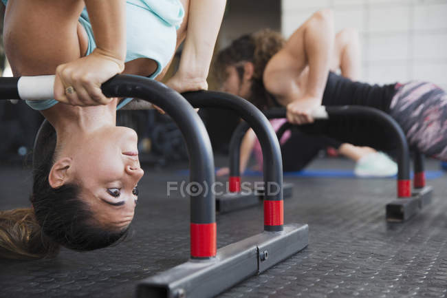 Focused young woman doing upside-down shoulder stand with equipment at gym — Stock Photo