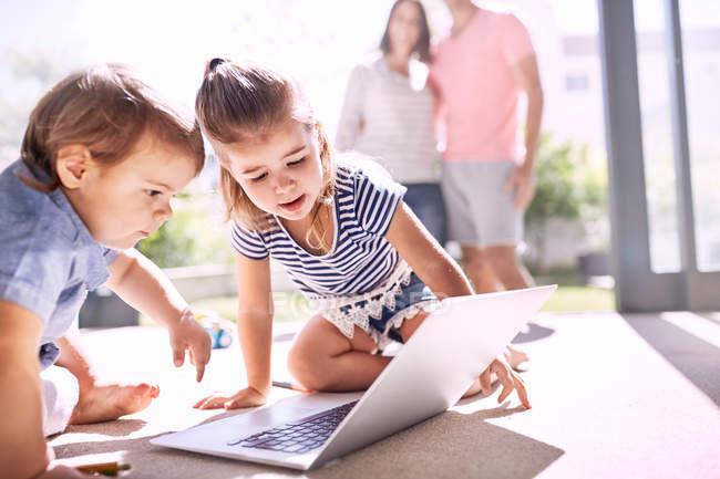 Bruder und Schwester mit Laptop auf sonnigem Boden — Stockfoto