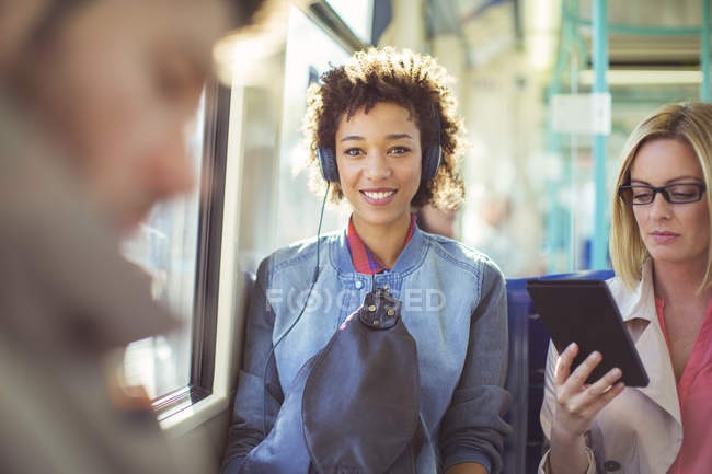 Woman listening to headphones on train — Stock Photo