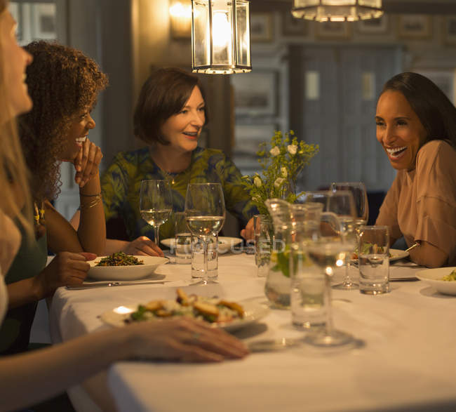 Women friends dining and talking at restaurant table — Stock Photo