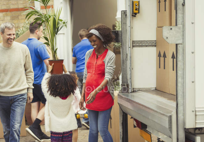 Multi-ethnic young family unloading moving van outside new house — Stock Photo