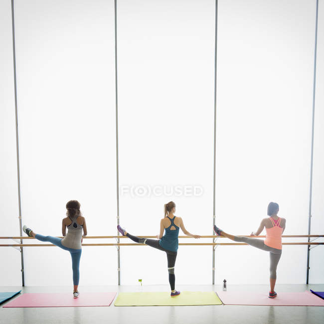 Women stretching legs at barre in exercise class gym studio — Stock Photo