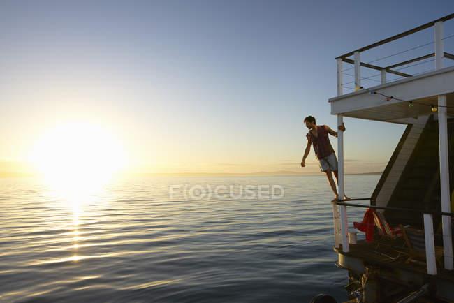 Людина, спершись на перила літніх houseboat над океаном під час заходу сонця — стокове фото