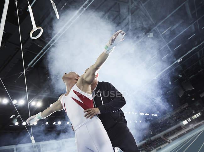 Тренер поднимает мужскую гимнастку ниже колец гимнастики на арене — стоковое фото