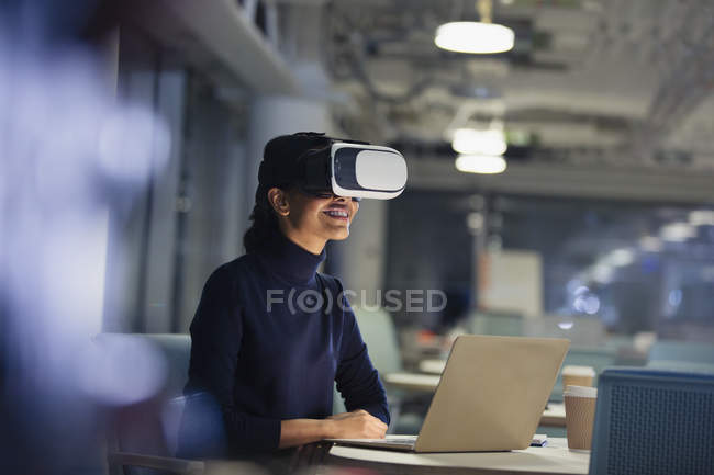 Businesswoman using virtual reality simulator at laptop in dark office — Stock Photo