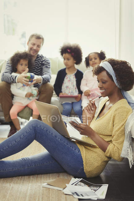 Multi-ethnic father and daughters playing behind mother working at laptop on living room floor — Stock Photo