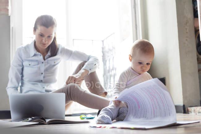 Curioso bambino figlia guardando documenti accanto alla madre che lavora al computer portatile — Foto stock