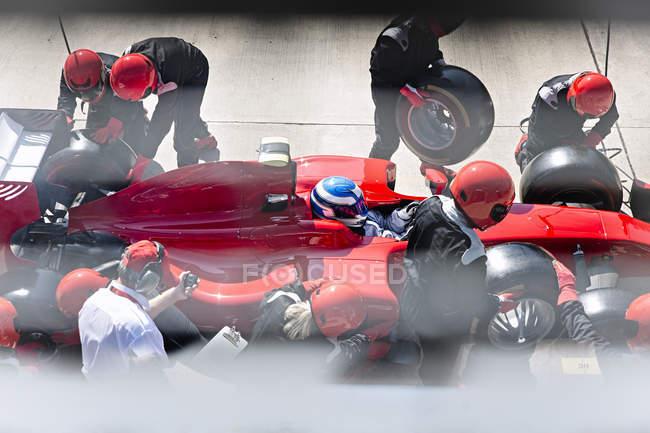 Менеджер з секундомір терміни яма екіпажем заміни шин на формули один гоночний автомобіль в піт-лейн — стокове фото