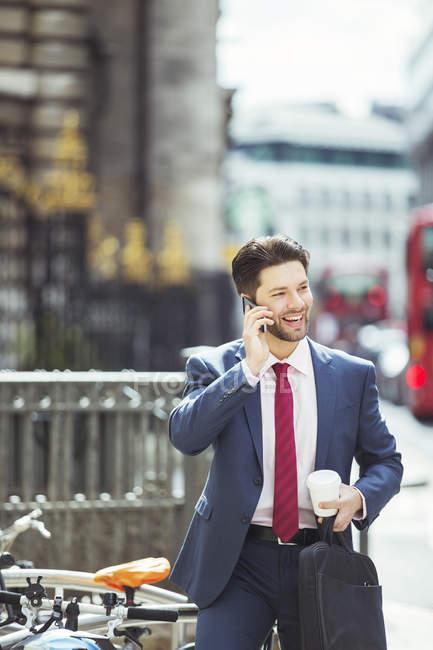 Homme d'affaires parlant sur le téléphone portable sur le trottoir de la ville — Photo de stock