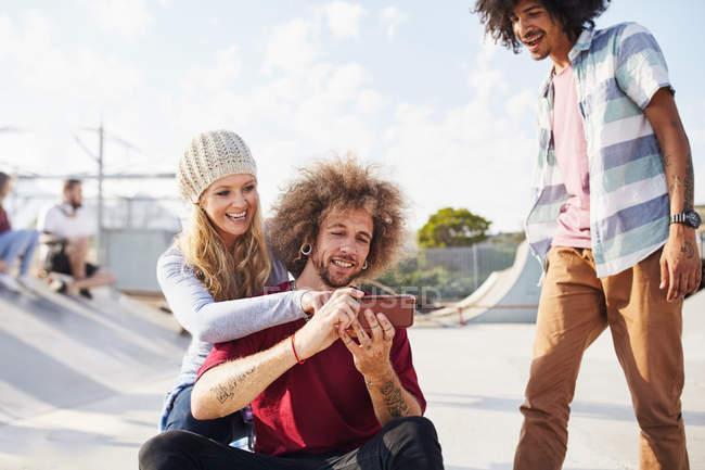 Amigos usando telefone inteligente no parque de skate ensolarado — Fotografia de Stock