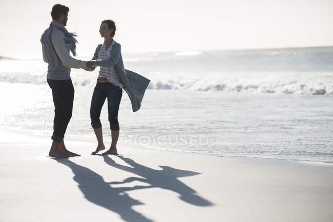 Молоді пара холдингу руки на пляжі — стокове фото