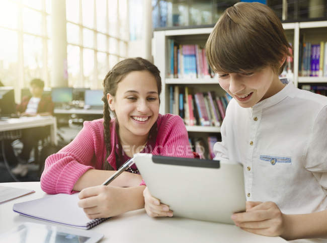 Smiling students researching, using digital tablet at table in library — стоковое фото