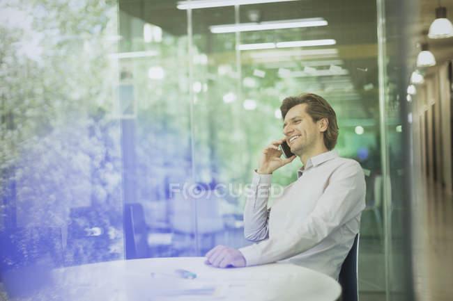 Hombre de negocios sonriente hablando por teléfono celular en la sala de conferencias - foto de stock