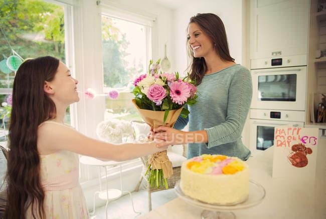 Hija cariñosa a ramo de flores para madre dia de las madres - foto de stock