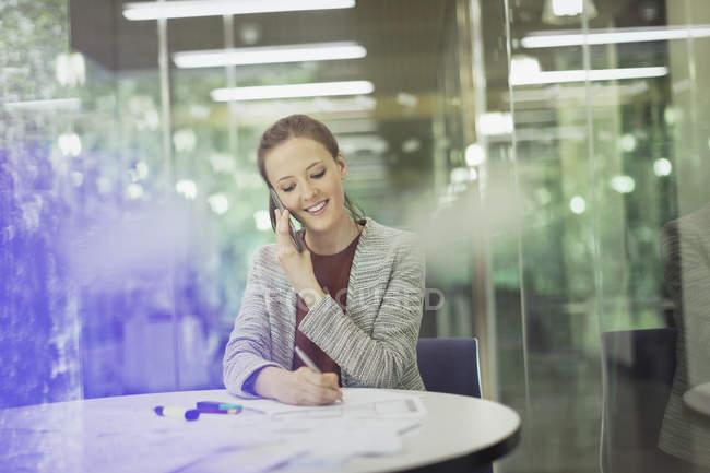 Donna d'affari sorridente che parla al cellulare e prende appunti in sala conferenze — Foto stock