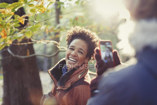 Smiling woman posing for boyfriend with camera phone in sunny autumn woods — Stock Photo