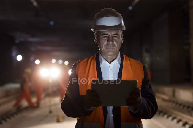Serious male foreman using digital tablet at dark construction site — Stock Photo