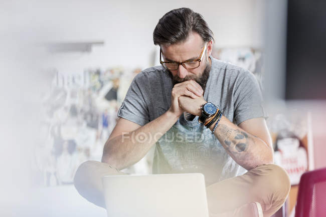 Pensive male design professional working at laptop — Stock Photo