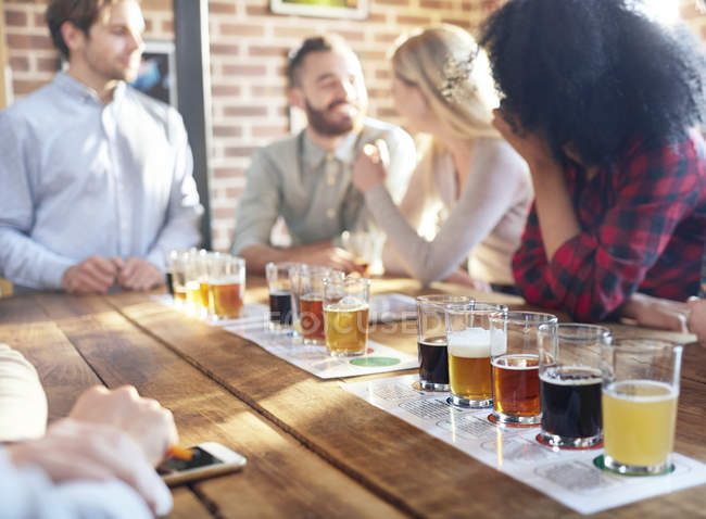 Friends tasting beer samples at brewery — Stock Photo
