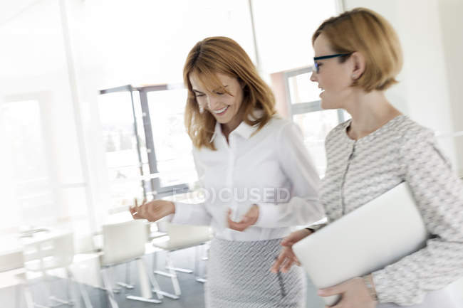 Businesswomen walking and talking in modern office — Stock Photo