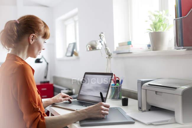 Progettazione mediante tavoletta grafica al computer portatile in ufficio — Foto stock
