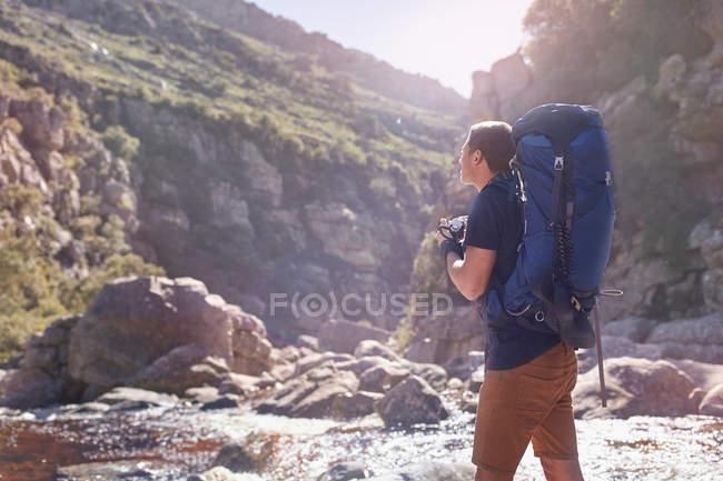 Молода людина з рюкзак, походи, фотографування з камери нижче Сонячна, віддалений скелі — стокове фото