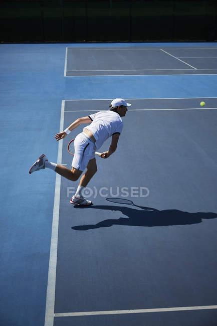 Чоловічий теніс гравець грає теніс на Сонячний синій тенісний корт — стокове фото