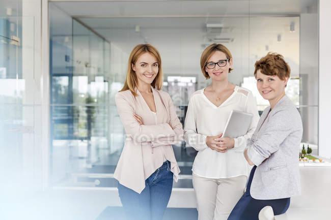 Portrait de femmes d'affaires souriantes dans un bureau moderne — Photo de stock