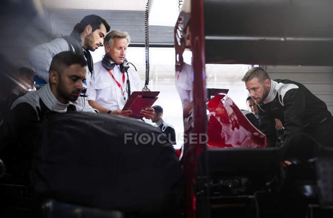 Gerente e motorista falando atrás da equipe pit trabalhando em carro de corrida na garagem de reparação — Fotografia de Stock