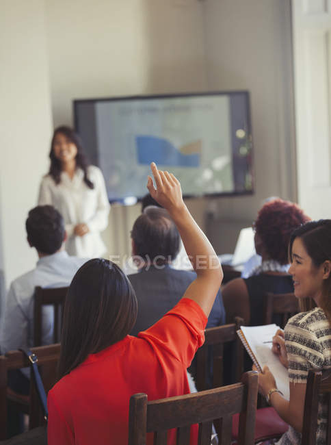 Businesswoman in audience asking question at business conference — Stock Photo