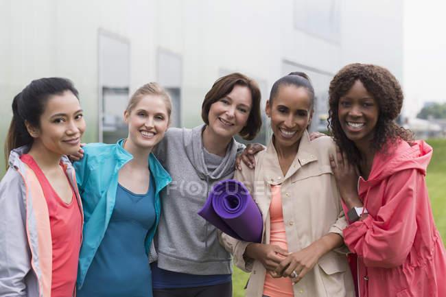 Portrait souriant femmes amis avec tapis de yoga — Photo de stock